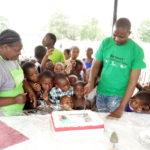 Small children gather for the treat of a piece of celebration cake