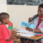 The children learn English early and this 5 year old is reading English words for a quiz